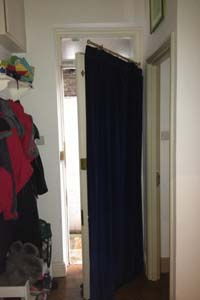 Portiere rod and interlined curtain fitted to Front Door in North London - the door is half open