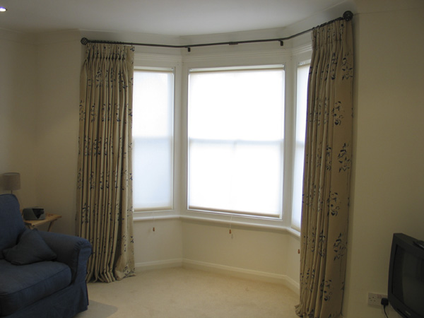 Sanderson printed linen, pinch pleats on a bay pole with roller blinds in this lower ground floor window