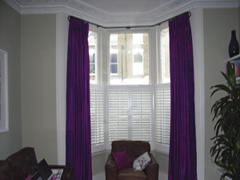 Silk curtains on bay window pole with cafe height shutters for privacy Highgate