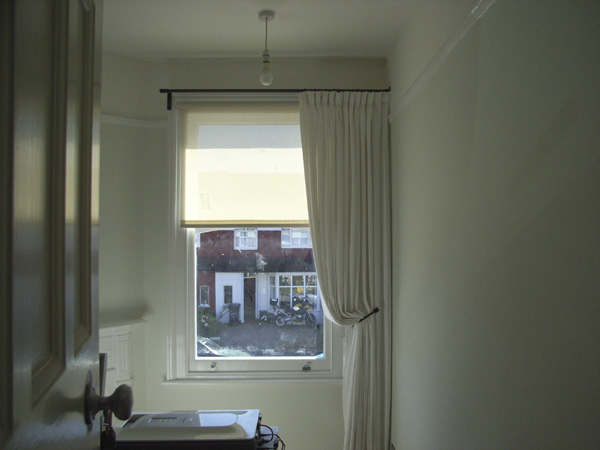 Single curtains can work well on asymetric windows - here the pole uses a recess bracket to attach to the side wall on one side a simple roller blind completes the picture