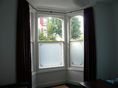 Artificial silk curtains on bay window pole Tufnell Park