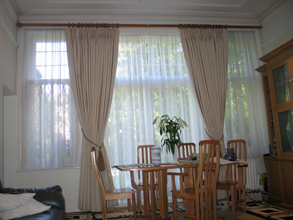 Calico curtains suspended from a 50mm wooden pole. Recess brackets at each end