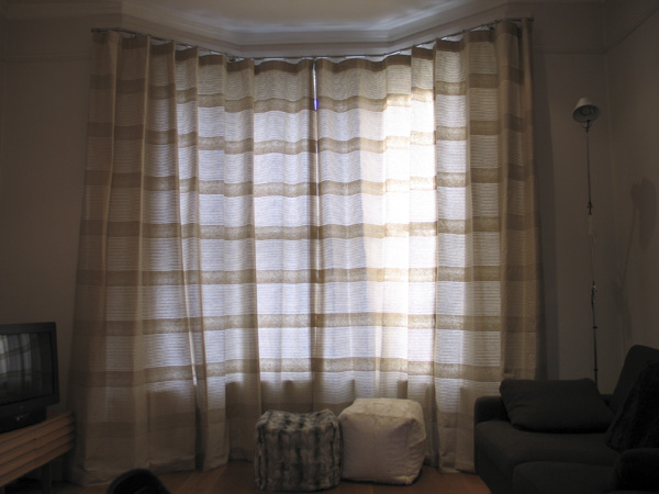 Linen curtains on a 25mm polished steel bay window pole from The Bradley Collection