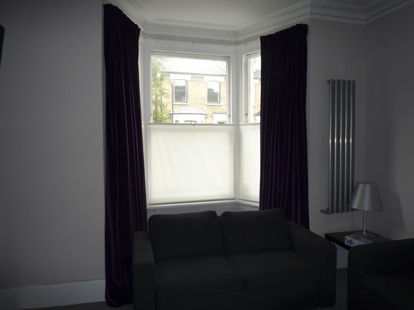 Velvet curtains, interlined and pinch-pleated, on corded steel bay window track together with simple bottom up blinds for privacy
