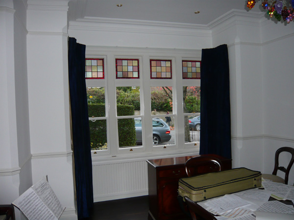 Faux silk curtains, interlined and pinch pleated, on a corded steel bay window track fitted to the top edge of the window architrave