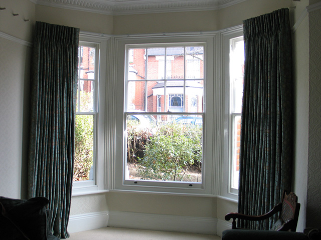 French cloque work in silk, interlined and pinch pleated curtains, corded steel bay window track fixed to the top edge of the window architrave