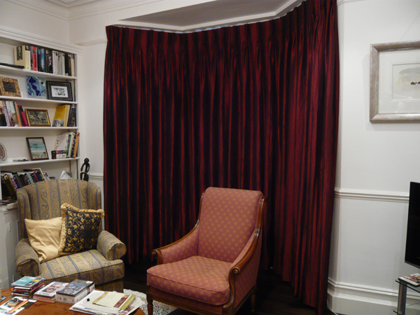 Faux silk interlined and pinch pleated on bay window track - closed