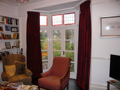 Red faux silk curtains, interlined and pinch pleated on a corded steel bay curtain track fitted to ceiling Muswell Hill