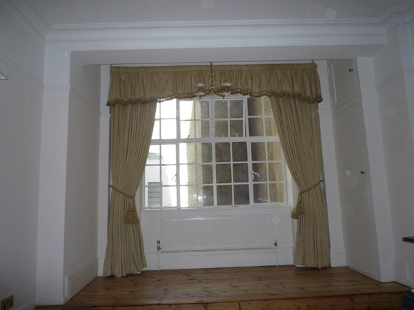 Gold damask curtains with gathered shaped pelmet with braid