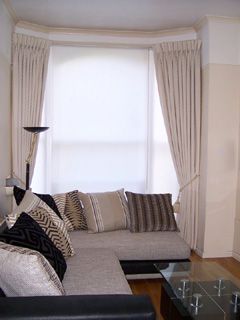 Goblet pleat curtains in cream damask on covered fascia with simple white roller blinds Archway