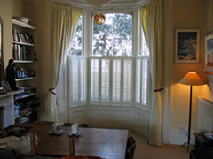 Simple lined linen curtains on bay rack with half-height shutters Islington