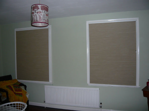 a pair of blackout duette blinds fully lowered inside side channels