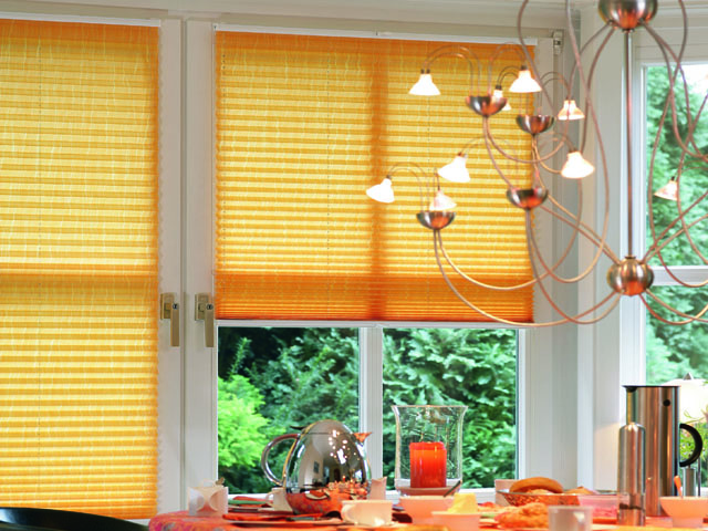 Yellow pleated blinds fitted to opening windows, attached top and bottom so that the windows operate normally