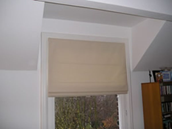 A simple Roman Blind leaves a small room appearing larger. With the top of this window set in a dormer there is very little space for curtains and curtains would reduce the amount of light available