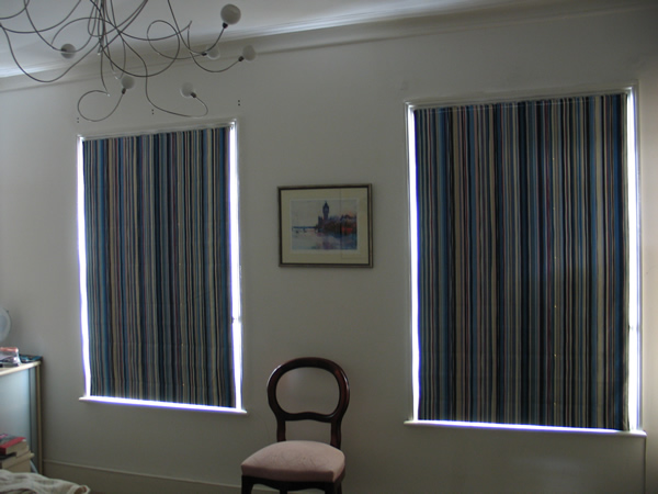 Blackout roman blinds - light does not pass through blackout lining but you do get light wash at the edges