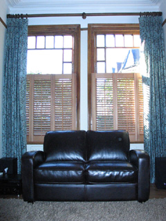 half height oiled cedar wood shutters with 47mm louvres, together with interlined, pinch pleat curtains Stroud Green