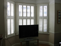 Wooden shutters with 47mm louvres, tier on tier in silk white Enfield
