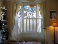 cafe height privacy shutters with linen curtains Islington