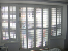 shutters in silk white wood with 63mm louvres are the only window treatment throughout this modern North London apartment Crouch End