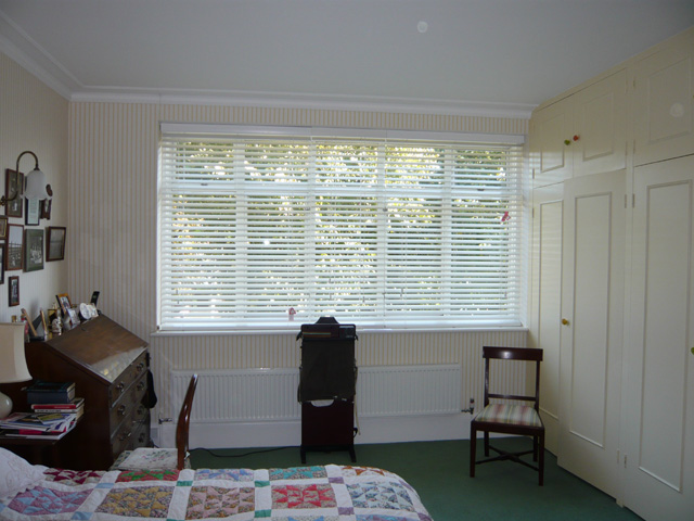 Three white 50mm slatted wood blinds - part closed