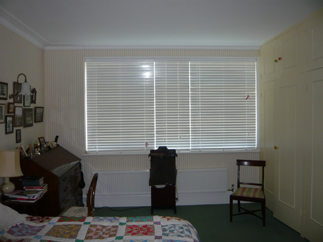 Three white 50mm slatted wood blinds - fully closed